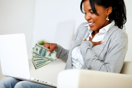 Portrait of an excited ambitious young woman with money while is sitting on sofa at home in front a laptop photo