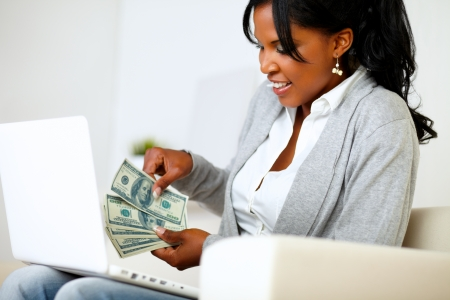 Portrait of an excited ambitious woman with dollars while is sitting on sofa at home in front a laptop