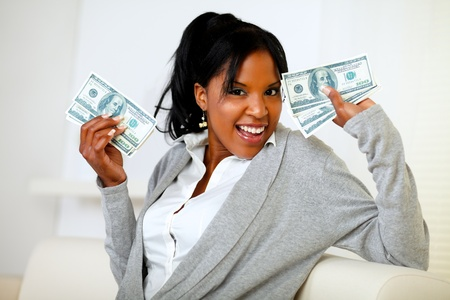 Portrait of an afro-american girl holding plenty of cash money while is looking to you photo