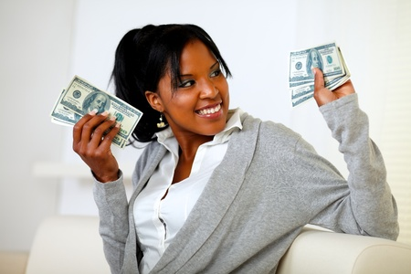 Portrait of a charming young woman holding plenty of cash money while is looking to his left photo