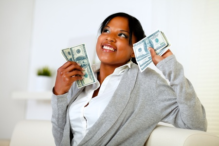 Portrait of a charming woman looking up and holding plenty of cash money at home indoor photo