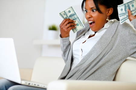 Portrait of a surprised woman holding plenty of cash money in front a laptop at home indoor