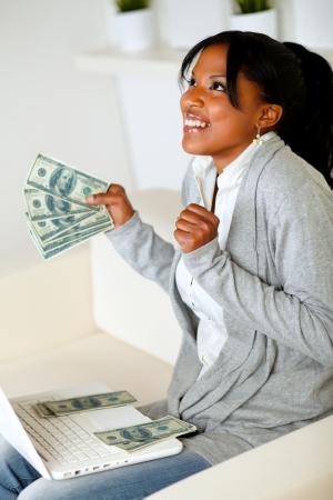 Portrait of a excited afro-american woman looking up with dollars on one hand while is sitting in front a laptop at home indoor photo