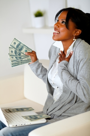 Portrait of a happy woman holding plenty of cash money while is looking up with hope Stock Photo