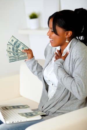 Portrait of a woman holding and looking plenty of cash money in front a laptop at home indoor photo