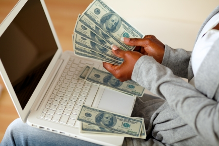 Portrait of a black woman counting plenty of cash money in front a laptop at home indoor photo