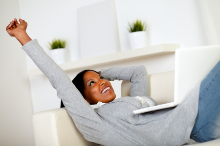 Portrait of a relaxed afro-American woman browsing the Internet on laptop while is lying on sofa at home indoor photo