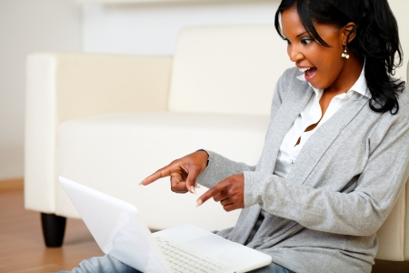 Portrait of an excited stylish woman pointing and looking to laptop screen while is sitting on the floor at home photo