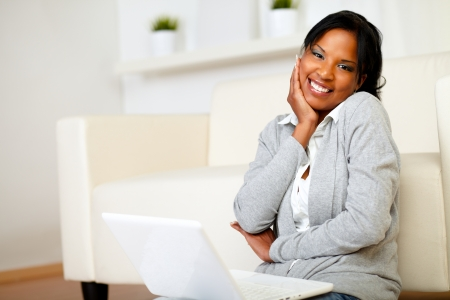 Portrait of a cute black woman smiling at you while is sitting on the floor with laptop photo