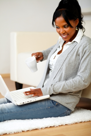 Portrait of a beautiful woman with a mug in front of her laptop photo