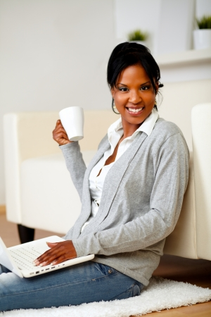 Portrait of a beautiful young woman with a mug in front of her laptop while is smiling and looking to you Stock Photo - 14641438
