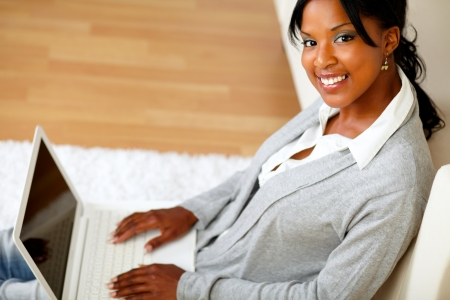 Top view portrait of a young woman with her laptop smiling at you while sitting on the floor at home indoor photo