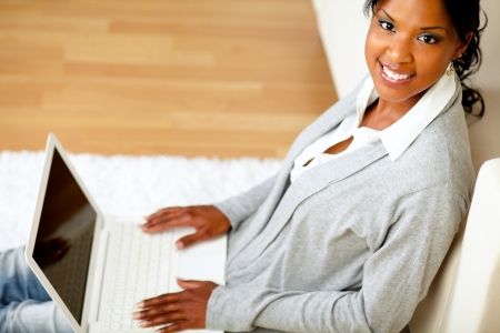 Top view portrait of a young girl smiling at you with her laptop while is sitting on the floor at home indoor photo