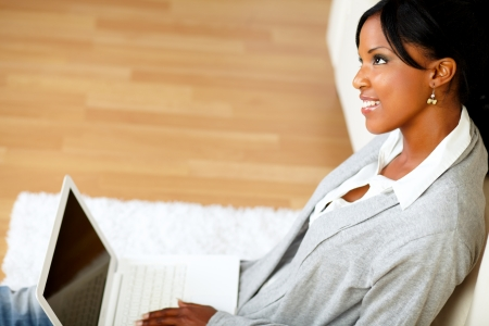 Portrait of a lovely young woman smiling and looking up while is sitting on the floor in front of her laptop photo