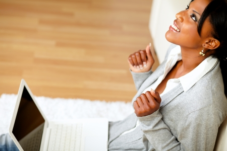 Portrait of a positive afro-american young woman looking up while sitting on the floor in front her laptop Stock Photo