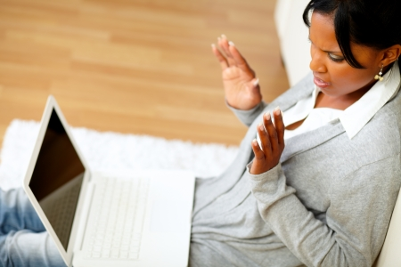 Top view portrait of a confused and surprised young woman reading a message on laptop screen while sitting on the floor at home indoor Stock Photo - 14641185