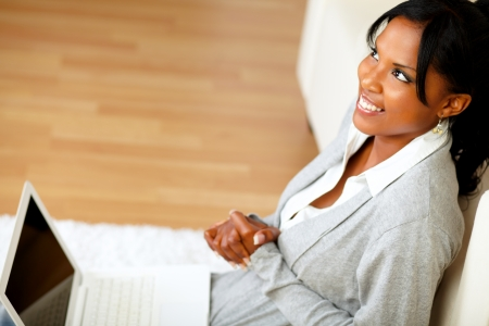 Top view portrait of a pretty woman sitting at home on the floor in front her laptop while is looking up Stock Photo - 14641204
