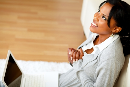 Top view portrait of a young black woman sitting at home on the floor in front her laptop while is looking up Stock Photo - 14641200