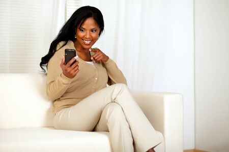 Portrait of an afro-American woman pointing her cellphone while sitting on a couch at home indoor photo