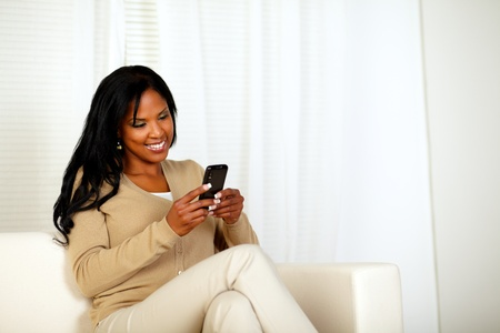 Portrait of a black woman sending a message by the cellphone while sitting on sofa Stock Photo - 14706451