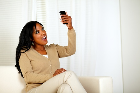 Portrait of a surprised woman holding her cellphone up while is reading a message at home indoor photo