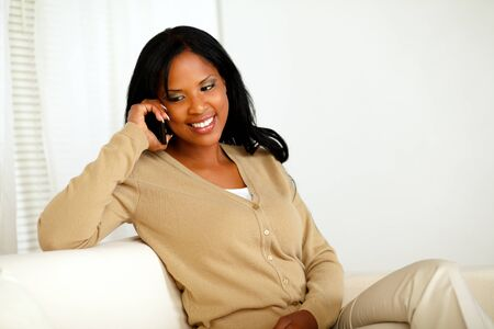 Portrait of a smiling young woman talking on cellphone while sitting on sofa at home indoor photo