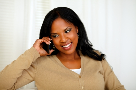 Portrait of an afro-American woman conversing on mobile phone at home indoor photo