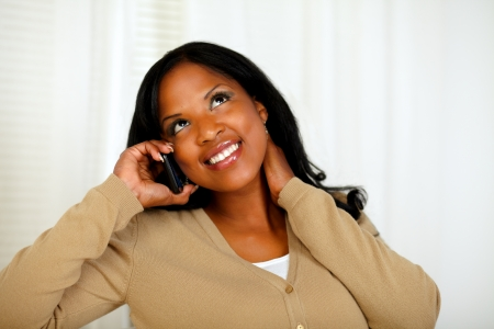 Portrait of a charming young woman conversing on mobile phone while is looking up at home photo