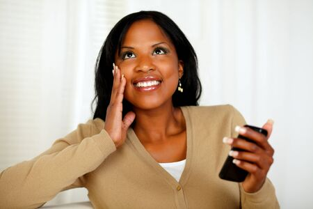 Portrait of a charming black woman holding a mobile phone while is looking up photo