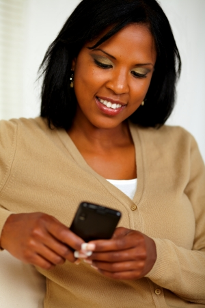 Portrait of a charming black woman sending message by her cellphone Stock Photo - 14706495