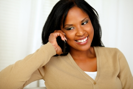 Portrait of a stylish young woman looking down while is on mobile phone at home photo