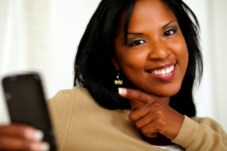 Portrait of a woman pointing her cellphone and smiling at you photo