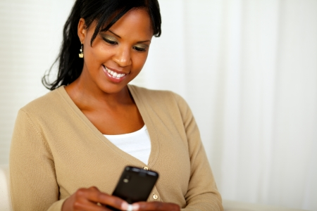 Portrait of a friendly black woman sending a message by her cellphone at home indoor photo