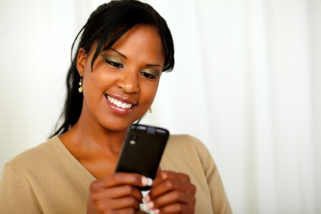 Portrait of an afro-American woman sending a message by her cellphone at home indoor photo