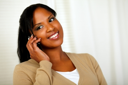 Portrait of a smiling young woman talking on cellphone at soft colors composition photo