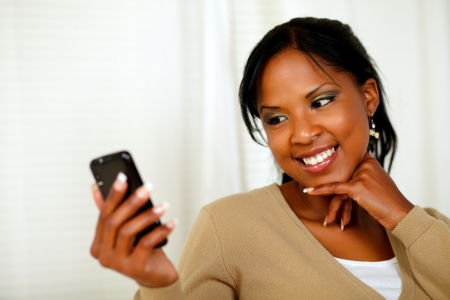 Portrait of a smiling female sending a message by the cellphone at home indoor photo