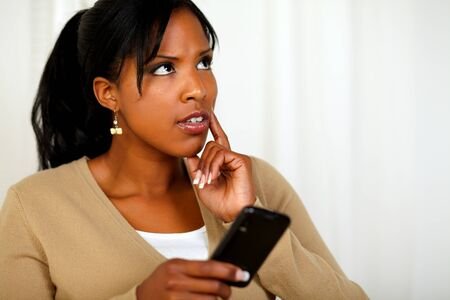 Portrait of a pensive black woman using her cellphone at soft colors composition Stock Photo - 14706618