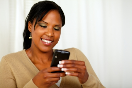 Portrait of an attractive young woman sending a text message with her mobile phone photo
