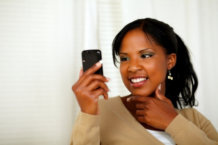 Portrait of a sophisticated woman reading a message on cellphone photo