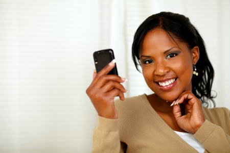 Portrait of a sophisticated lady reading a message on cellphone while looking at you photo