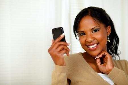 persona llamando: Retrato de una dama sofisticada leer un mensaje en el teléfono celular mientras te mira