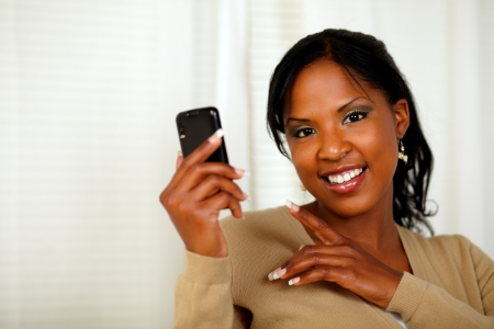 Portrait of a charming woman reading a message on cellphone while looking at you photo