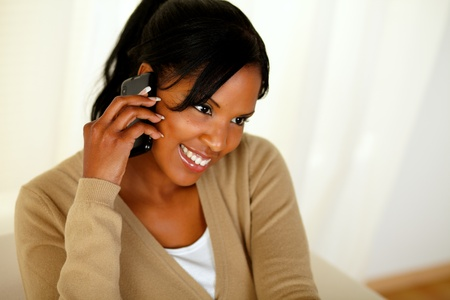 Portrait of an afro-American woman speaking on mobile phone at home indoor photo