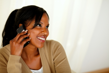 Top view portrait of an afro-American young woman conversing on cellphone while is looking up photo