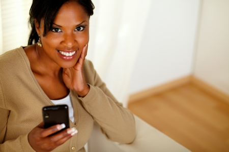 Top view portrait of a young afro-american woman sending a message while smiling at you at home photo