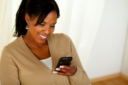 Portrait of a young afro-american woman reading a message on cellphone at home indoor photo