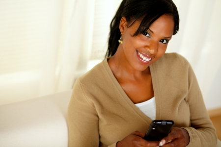 Portrait of a smiling woman looking at you while sending a message with her cellphone photo