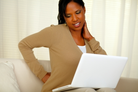 Portrait of a young woman with back pain working on laptop while sitting on sofa at home indoor Stock Photo - 14795047