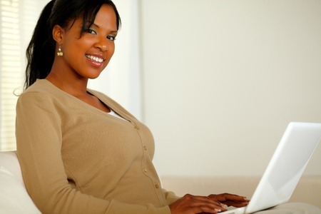 Portrait of a pretty girl smiling at you while working on laptop at home indoor photo