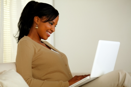 Portrait of a smiling woman browsing the Internet on her laptop while sitting on sofa at home photo